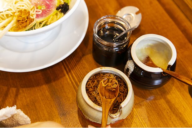 卓上にはフライドオニオン、焦がしネギ、黒七味、にんにく、生姜など薬味も充実。自分好みの味変も楽しもう