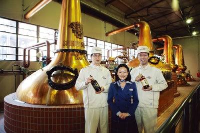 12基の蒸留釜の前で醸造技師の松田さん(左)や山谷さん(右)たちが、お待ちかね。釜の形や大きさで味も変わるそう