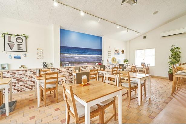 海のカフェをイメージ。白い壁に地元海岸の写真が飾られる / Cafe&Lunch Smile