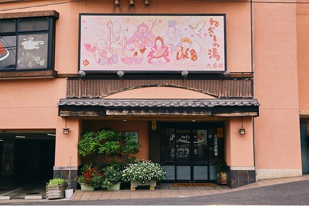 横浜市磯子区にある「ねぎしの湯 大盛舘」。ピンクの鮮やかな外壁に純和風の瓦屋根を合わせた、モダンな温泉旅館のような佇まい。七福神のイラスト看板も目印