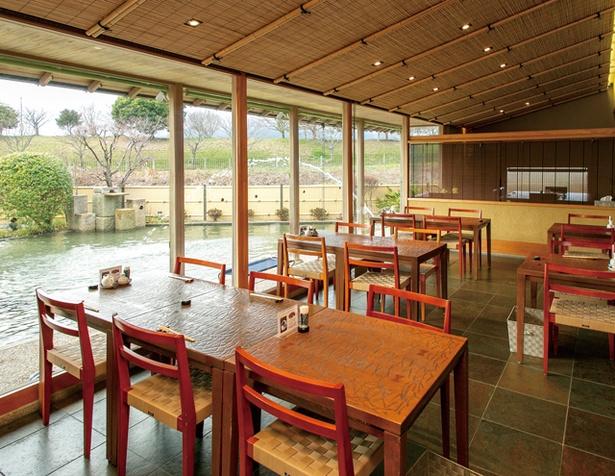 【写真を見る】肉匠 と川 / テーブル席と半個室を完備。庭越しにサクラ並木が見える