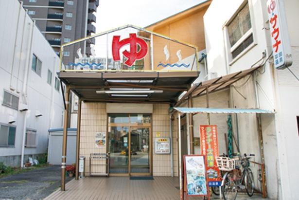 切り妻形の建物中央に「ゆ」を配したネオンが目印 / 平田温泉