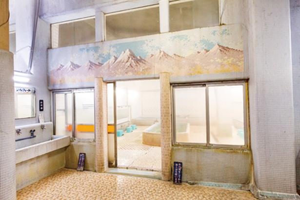 女湯の浴室入口の上部には、北アルプスと思われるタイル絵の装飾がある / 金時湯