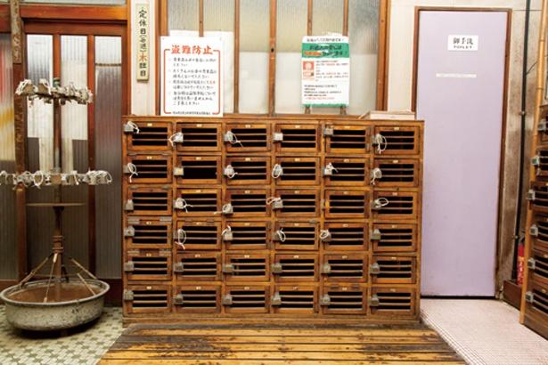 創業当時の面影を残す、木製のげた箱とその横に置かれた傘立ても要チェックだ / 金時湯