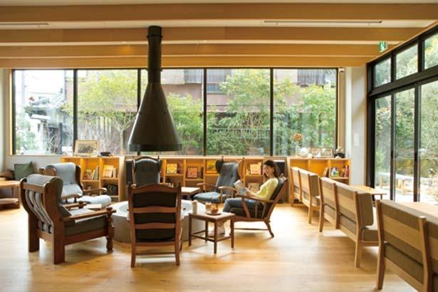 暖炉や窓に向いたテーブル席などくつろぎの空間(席の配置換えあり)/YADO Cafe