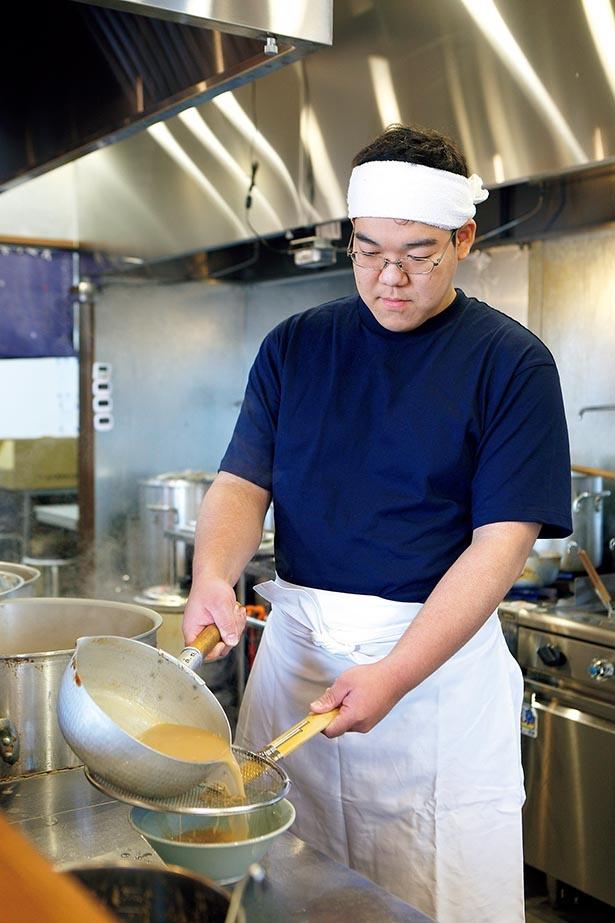 気を配りつつスープを丼に入れる店長・田村さん