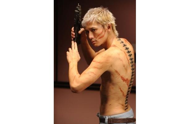 背中に背骨の刺青のある、背骨を演じる安藤の鍛え抜かれた美しい体を初披露