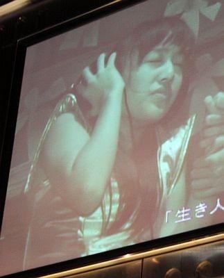 「生き人形 蒼の間」を体験し、リアルなサウンドにビビる百田夏菜子さんがスクリーンに映し出された