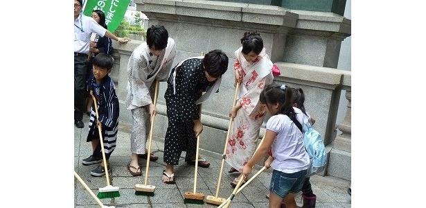 子供たちと一緒にブラシで日本橋を磨くキャストたち