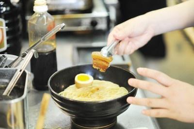 ●証拠保全(改良)ー トッピングでもうひとアクセント。味付け卵に加えてのせるのは、このメニュー専用に仕込んだ豚の角煮。溜ならではの味を強調する名わき役の誕生だ。