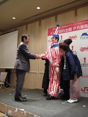 熊本県観光経済交流局長の佐伯和典さんにPR隊長のタスキをかけられる「くいだおれ太郎」
