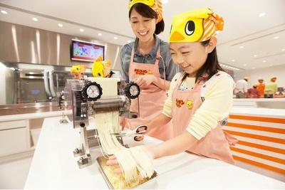 製麺機から出てくる麺を切り出すところ。「チキンラーメンファクトリー」の参加者は全員「ひよこちゃんバンダナ」をもらえる