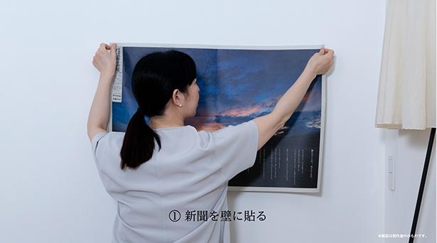 新聞紙面を壁に貼り付ける