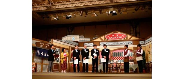 吉本新喜劇の舞台に登場する内場勝則、未知やすえ、藤井隆、すっちー。蝶ネクタイ姿の吉本社員はプロジェクト概要を練習という態でプレゼン