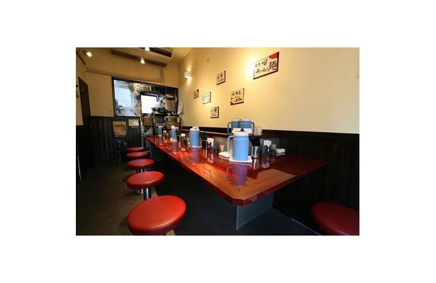 【麺仙 葵賀佐】ワインレッドのカウンターと椅子に、白い壁や白い器が映える明るい店内。店内のポップもモノトーン×赤が基調。元気なスタッフの心意気もいい