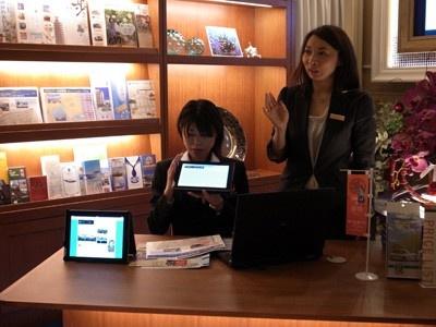 コンシェルジュがipadなどを使用しながら、神戸の観光情報を教えてくれる
