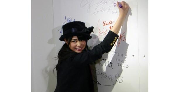 ボードにサインするAKB48の前田亜美