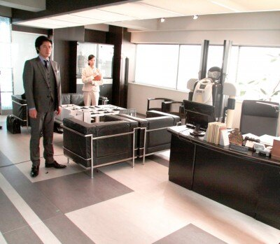 ビルの最上階にあり、奥に介護用ロボットが置いてある社長室。窓ははめ殺しで... ビルの最上階にあ