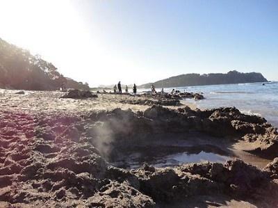 ニュージーランドの「ホットウォータービーチ」。干潮時にスコップを持った人が集まり、波打ち際を掘り出すと、あっという間にプライベート温泉に