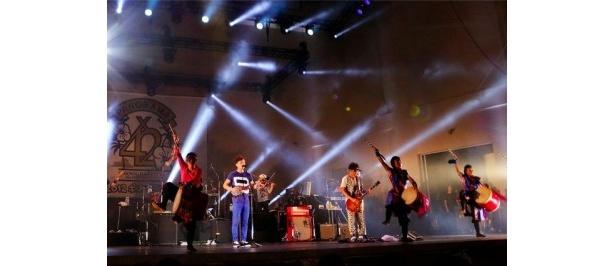 【写真を見る】エイサー隊とのステージでは沖縄の伝統楽器・三線も披露