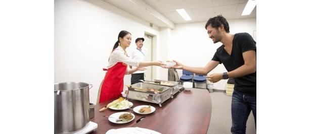 武井がスタッフに夜食を手渡し。男性スタッフは恐縮しながらも笑顔がこぼれる