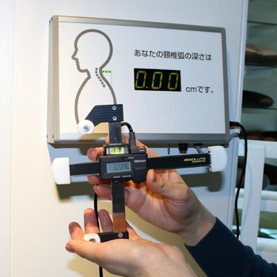 頭と首の差を測る機械。ちなみに記者の差は2.6センチメートル「ロフテー」(本社ショールーム)