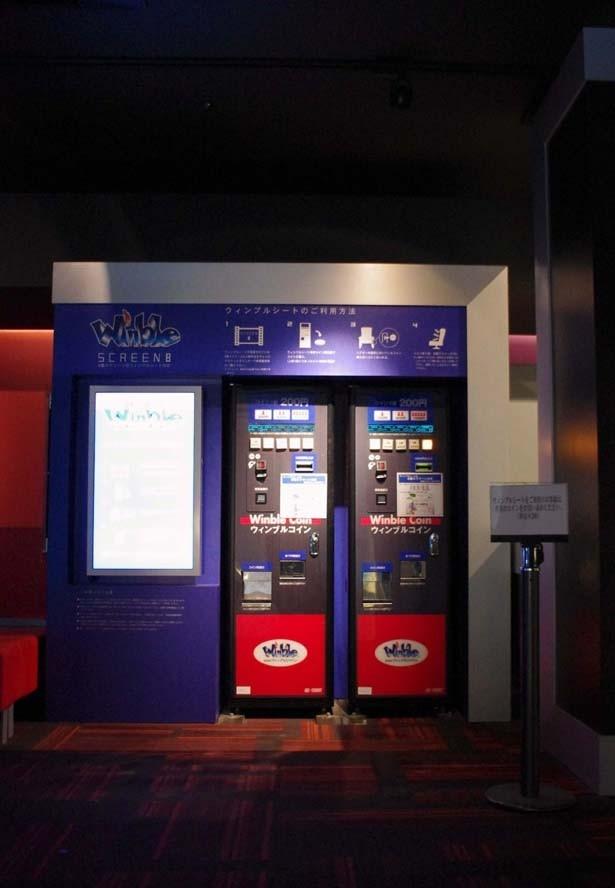 「ウィンブルシート」を作動させる専用のコインは劇場外の販売機で買うことができる