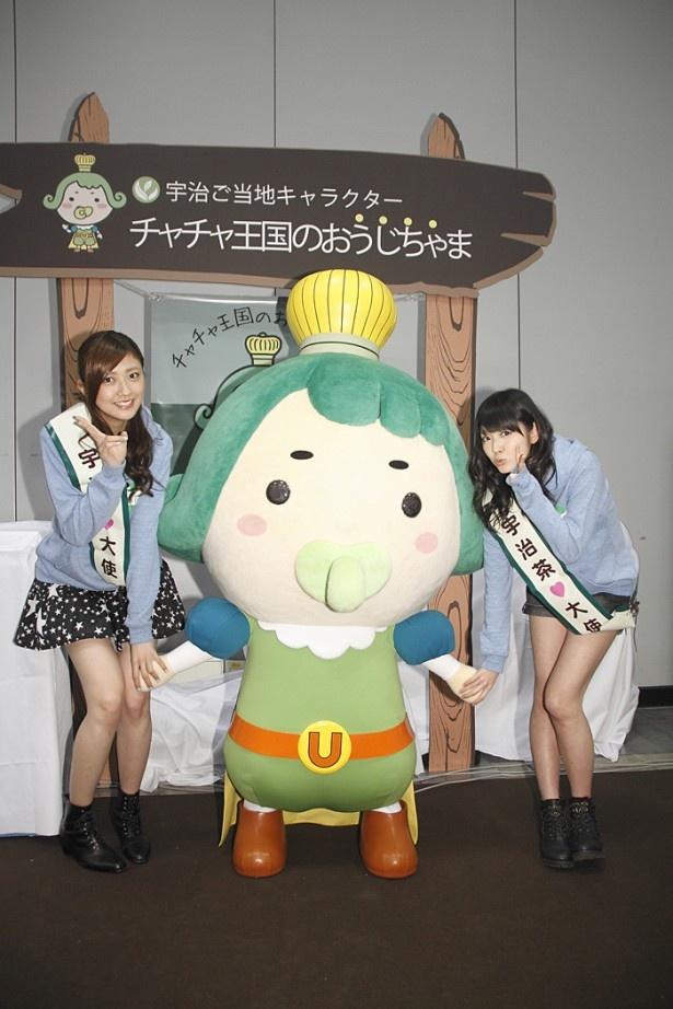 """ゆるキャラ""""チャチャ王国のおうじちゃま""""をはさんで熊井(左)と鈴木(右)はニッコリ"""