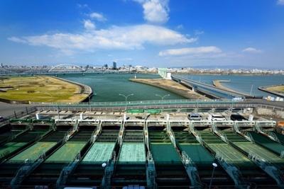 毛馬排水機場の北側、淀川を望む。手前の緑の装置は、大川から流れ込む水のごみを漉しとる役割をもつ