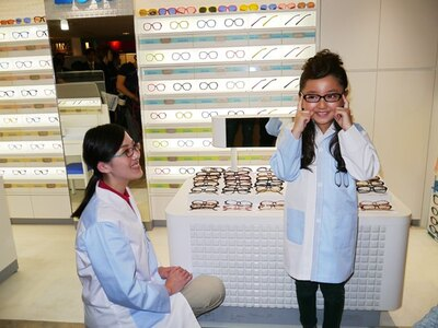 店頭に様々並んだメガネを実際に手にとって合わせる花音ちゃん