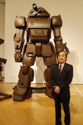 本展覧会の出品作家、大河原邦男。後ろには自身がデザインした1/1モデルのスコープドッグ