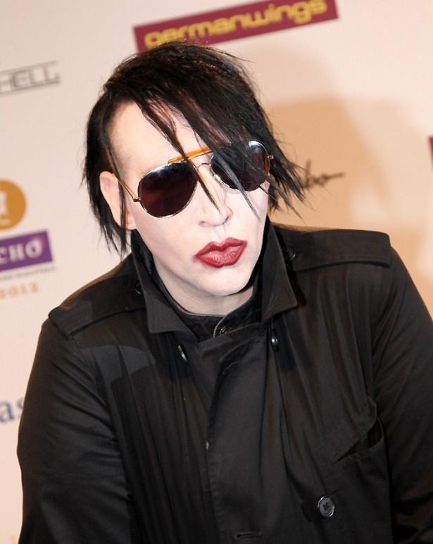 黒のアイライナーと口紅を塗り、黒い革のジャケットを着用している