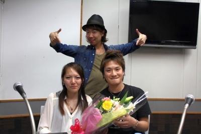 サプライズプロポーズをしたカップルと記念撮影するハジ→(写真後方)