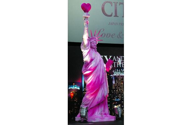 右手にはハート、左手にはクラッチバッグを持ったSATCオリジナルの自由の女神も登場