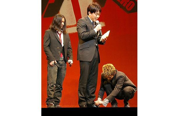 突然会場に上げられたTBSの安住紳一郎アナ。ほどけた靴ひもを結んであげる小栗
