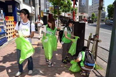 大通り沿いの歩道でゴミを拾う参加者たち
