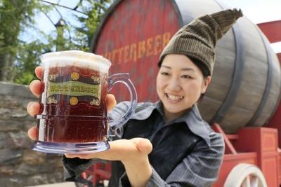 【写真を見る】黒ビールのような見た目だけど、まったく苦くない!「バタービール」販売用のカートとスタッフ