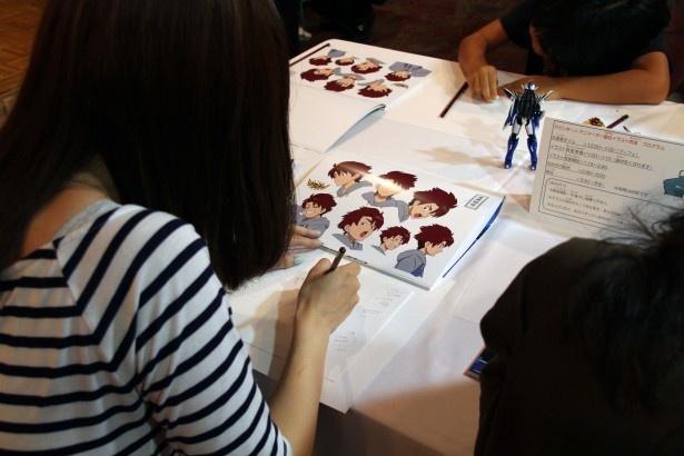 キャラクターの模写に取り組む参加者。トレーシングペーパーを使っておおまかな描き方を覚えてから清書していた