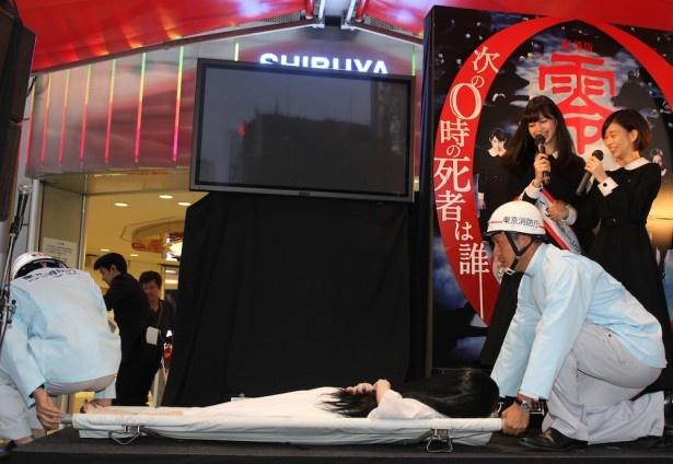 【写真を見る】貞子が救急隊員に担架で運ばれる!貞子はお行儀良く美しい姿勢で担架に乗り込んだ