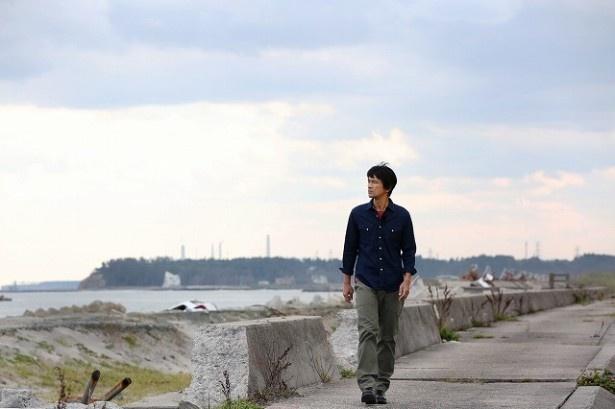 【写真を見る】津波が起きた海岸沿いを歩く