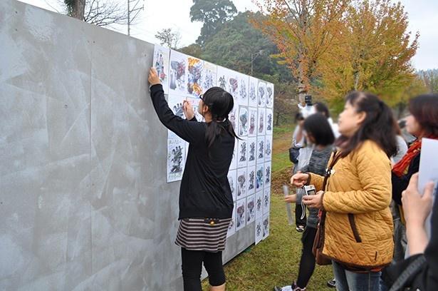 描かれたイラストを壁に貼り、集まったファンと一緒に作った壁画が完成!