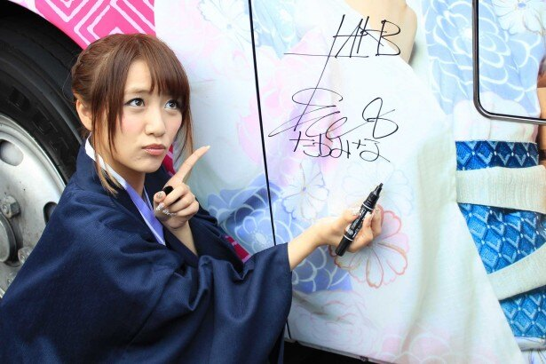 AKB48ラッピングバスにサインとメッセージを書く高橋みなみ