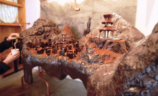 【写真を見る】チョコレートに見立てられたおいしそうなジオラマの街!蛇口をひねるとホットチョコレートが出る仕掛けも楽しい