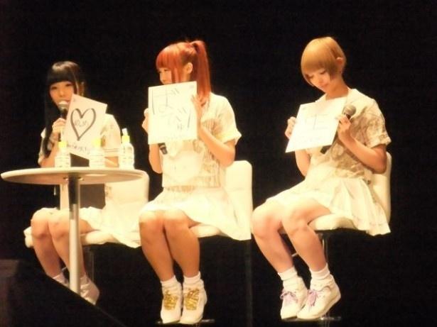 来場者へプレゼントする直筆色紙の説明をする相沢梨紗(左)、成瀬瑛美(中央)、最上もが(右)