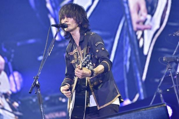 """力強くギターを掲げるボーカルの藤原基央。愛称は""""藤くん"""""""