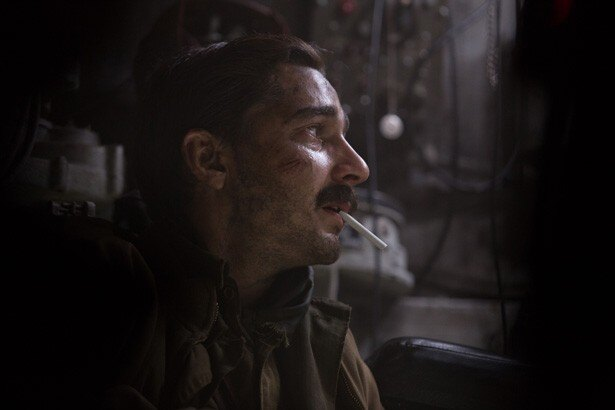 暗い戦車の中、煙草をくわえて何かを見上げているシャイア・ラブーフ演じるバイブル