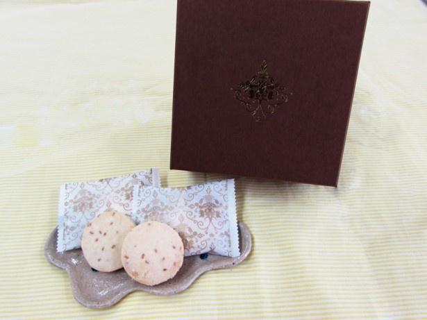 「金胡麻ちんすこう」(1500円・税別、16個入り)のパッケージは茶色。今までのちんすこうのイメージを覆すような、琉球豚のアグーやヤンバルクイナをモチーフにした装いが美しい