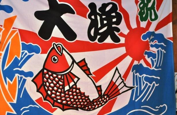 店内の壁には大漁旗がかけられ、本場のかき小屋の雰囲気が楽しめる。