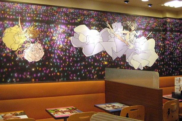 客席のサイリウムに照らされて舞うアイドルたちが壁面全体を飾っているロッテリア池袋西武前店のコラボレーションフロア
