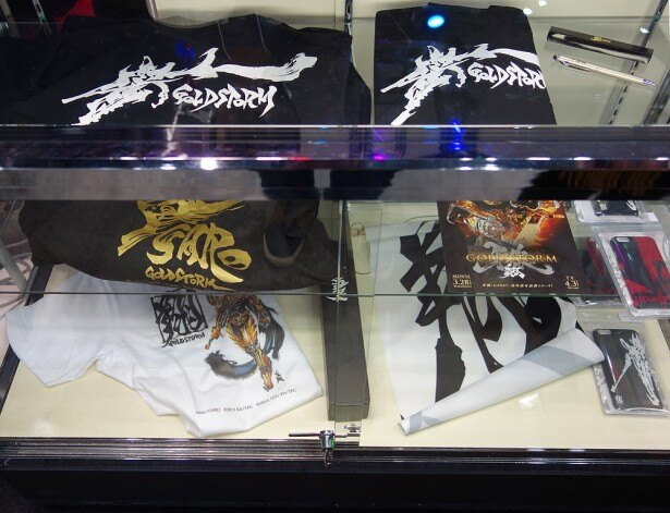 グッズコーナーでは、Tシャツ(3000円)やiPhone6ケース(2500円)などが販売されている